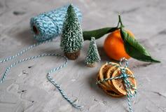 Mandarino di legno del canestro con le foglie e le luci, arancia del mandarino sulle decorazioni di anno di Gray Table Background fotografie stock