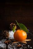 Mandarino sui bordi di legno con il cono di abete e della neve Fotografia Stock