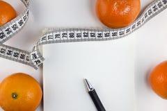 Mandarins, blocnote, centimeterband op het witte op dieet zijn als achtergrond stock foto's