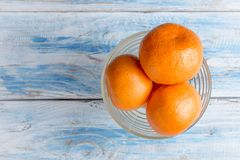 Mandarins in a bowl on wooden table.top view. stock images