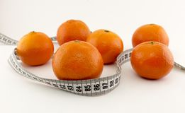 Mandarins and centimeter tape on a white background fruit stock image