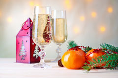 Mandarins, champagne, fir-tree branch and house shaped candlestick Royalty Free Stock Photo