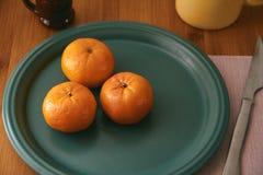 mandarins Close-up das tangerinas em uma placa e com elementos de tabela tais como o copo e a cutelaria Parte traseira de madeira fotos de stock royalty free