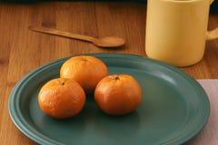 mandarins Close-up van mandarijnen op een plaat en met lijstelementen zoals kop en bestek Houten rug Mandarin achtergrond stock afbeeldingen