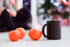 Mandarins and cup. Three mandarins and cup on wooden floor Royalty Free Stock Photos