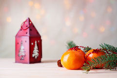 Mandarins with fir-tree branch and house shaped candlestick Royalty Free Stock Photography