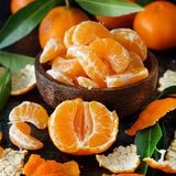 Mandarins with leaves in a bowl. On a dark background Stock Image