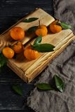 Mandarins with leaves on a wooden box. royalty free stock image