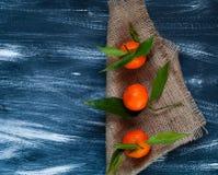 Mandarins met groene bladeren op jute op een donkere houten achtergrond Royalty-vrije Stock Afbeelding