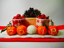 Mandarins with number 2018 on the background of a basket with pine cones and winter christmas mugs, painted snowflakes and Chri royalty free stock photo