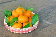 Mandarins orange fruit with green leaf in basket on wooden floor. The mandarins orange fruit with green leaf in basket on wooden floor Stock Photos