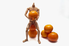 Mandarins and plastic doll Stock Photos
