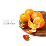 Mandarins and strawberries on wooden board Royalty Free Stock Photos