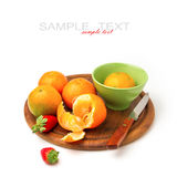 Mandarins and strawberries on wooden board Stock Image