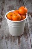 Mandarins in white metal bucket. Mandarins in a white metal bucket on the wooden floor Royalty Free Stock Photo