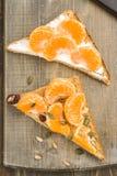 Mandaryn pomarańcze i sosnowe dokrętki na wholemeal chleba trójbokach zdjęcia royalty free