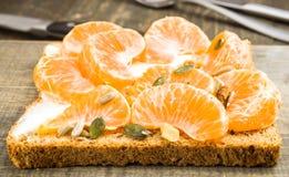 Mandaryn pomarańcze segmenty na wholemeal chlebie obraz stock