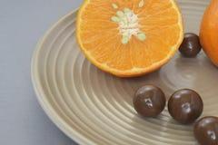 Mandaryn z czekoladowym dragee w beżowym ceramicznym talerzu zdjęcie royalty free