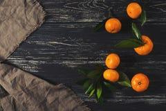 Mandaryny z liśćmi na starej ciemnej drewnianej powierzchni z bieliźnianą pieluchą Odgórny widok zdjęcie stock