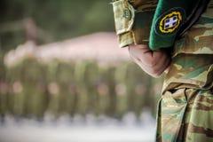 Mande la mano del ` s que sostiene la boina durante juramento en el ejército griego imagenes de archivo