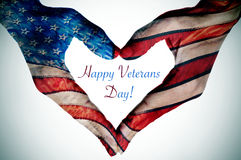 Mande un SMS al día y a las manos de veteranos feliz que forman un corazón con la bandera Foto de archivo