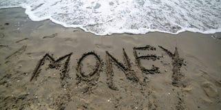 mande un SMS al DINERO en la arena del mar fotografía de archivo libre de regalías