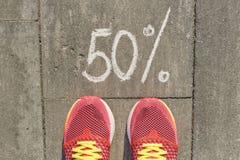 Mande un SMS al 50 por ciento escrito en el pavimento gris con las piernas de la mujer en zapatillas de deporte, visión desde arr fotografía de archivo libre de regalías