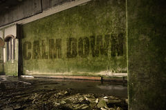 Mande un SMS calman abajo en la pared sucia en una casa arruinada abandonada Foto de archivo libre de regalías