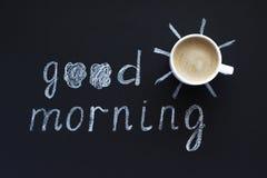 Mande un SMS a la buena mañana, tiza del sol en el fondo negro, taza de café, imagen de archivo libre de regalías