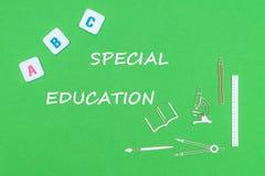 Mande un SMS a la educación especial, desde arriba de fuentes de escuela de madera de los minitures y de letras del ABC en fondo  Foto de archivo