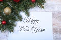 Mande un SMS a la Feliz Año Nuevo en el papel con el piel-árbol, las ramas, las bolas de cristal coloreadas, la decoración y los  Imágenes de archivo libres de regalías