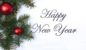 Mande un SMS a la Feliz Año Nuevo en el papel con el piel-árbol, las ramas, las bolas de cristal coloreadas, la decoración y los  Fotografía de archivo