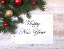 Mande un SMS a la Feliz Año Nuevo en el papel con el piel-árbol, las ramas, las bolas de cristal coloreadas, la decoración y los  Fotos de archivo