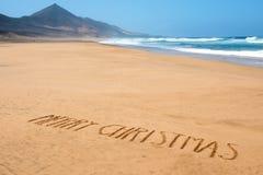 Mande un SMS a la Feliz Navidad en la arena de una playa Fotografía de archivo libre de regalías