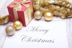 Mande un SMS a la Feliz Navidad en el papel con la caja de regalo y muchas bolas Foto de archivo libre de regalías