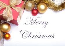 Mande un SMS a la Feliz Navidad en el papel con la caja de regalo y muchas bolas Fotos de archivo libres de regalías