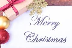 Mande un SMS a la Feliz Navidad en el papel con muchas bolas y cajas de regalo Imagenes de archivo