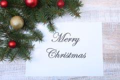 Mande un SMS a la Feliz Navidad en el papel con el piel-árbol, las ramas, las bolas de cristal coloreadas, la decoración y los co Imagen de archivo