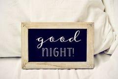 Mande un SMS a las buenas noches en una pizarra en una cama Imagen de archivo libre de regalías