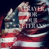 Mande un SMS a un rezo para nuestros veteranos y la bandera de los E.E.U.U. imagen de archivo libre de regalías