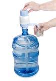 Mandefles met drinkwater, handpomp en een glas in een man han Royalty-vrije Stock Afbeeldingen