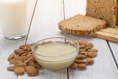 Mandel-Butter in einer Glasschüssel mit Milch und Brot lizenzfreie stockfotografie