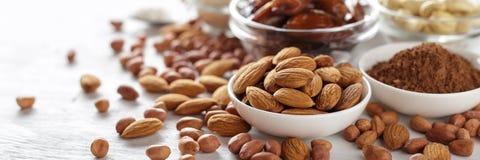 Mandel, Erdnuss, Kakaopulver und Acajoubaum auf weißem Holztisch Stockbilder