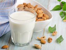 Mandeln mjölkar i exponeringsglas med mandlar Fotografering för Bildbyråer
