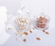 Mandeln und Pistazie in der Glasschüssel auf einem Hintergrund Stockfotografie