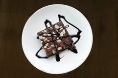Mandelschokoladenkuchenkuchen auf einer weißen Platte Stockbilder