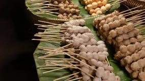 Manden met BBQ vleesballetjes op straat Stapels heerlijke traditionele barbecuevleesballetjes op stokken die op groene palm worde stock video
