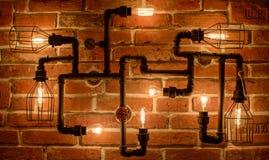 Mandi in aria la lampada con le lampade di Edison su un fondo del muro di mattoni Fotografia Stock