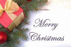 Mandi un sms al Buon Natale su carta con l'pelliccia-albero, i rami, le palle di vetro colorate, la decorazione ed i coni su un f Fotografia Stock