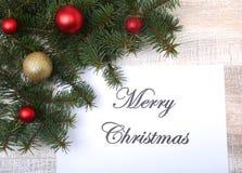 Mandi un sms al Buon Natale su carta con l'pelliccia-albero, i rami, le palle di vetro colorate, la decorazione ed i coni su un f Fotografie Stock
